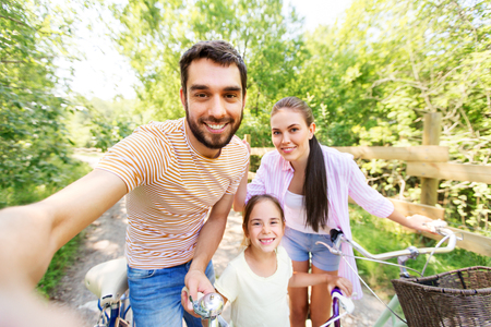 happy family with bicycles taking selfie in summer