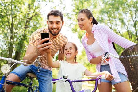 Familie mit Smartphone und Fahrrädern im Sommerpark