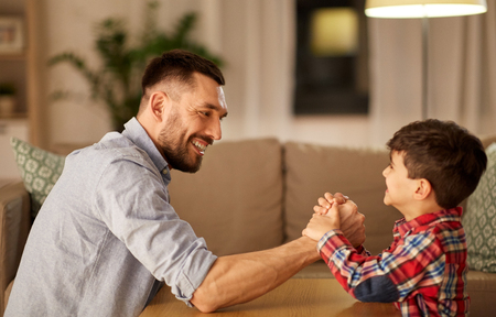 happy father and little son arm wrestling at home