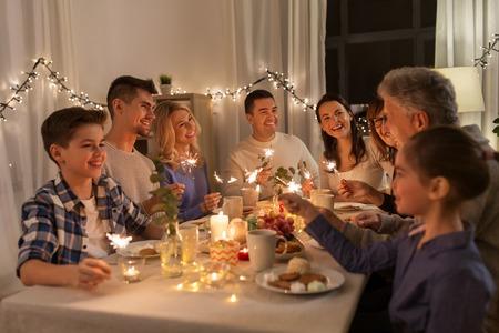 famille avec des cierges magiques en train de dîner à la maison