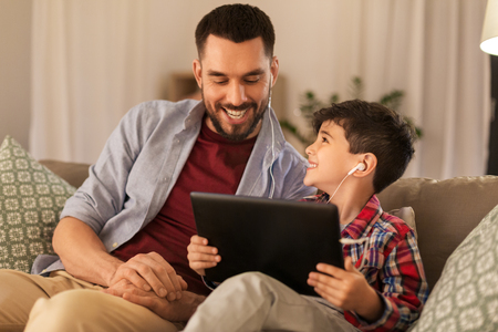 father and son listening to music on tablet pc