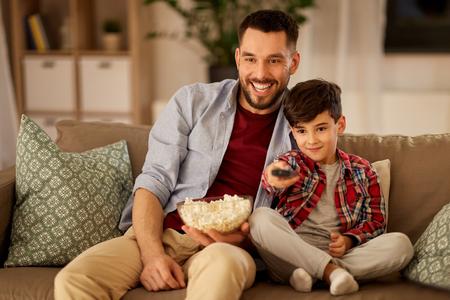 padre e hijo con palomitas de maíz viendo la televisión en casa