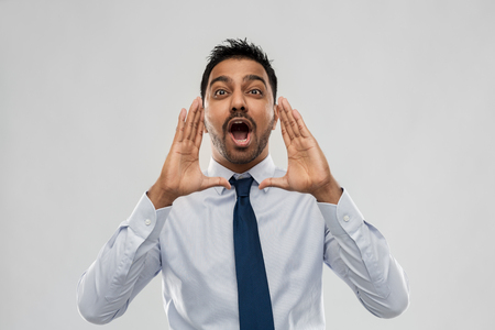 indian businessman shouting or calling over grey