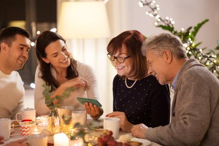 famille heureuse avec smartphone au goûter à la maison Banque d'images