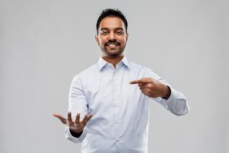 indian businessman holding something invisible