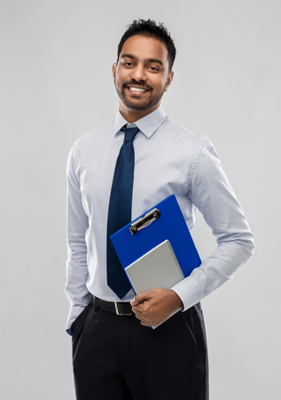indian businessman with clipboard and notebook