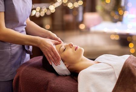 persone, bellezza, stile di vita e concetto di relax - bella giovane donna sdraiata con gli occhi chiusi e con massaggio viso e testa alla spa at Archivio Fotografico