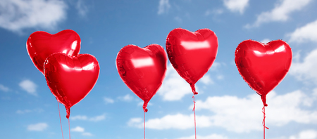 five red heart shaped helium balloons on white