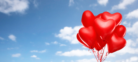 red heart shaped helium balloons on white 写真素材
