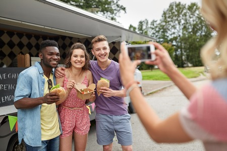 woman photographing friends eating at food truck