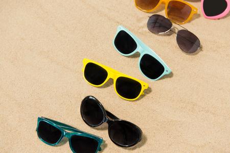 different sunglasses on beach sand Stock Photo