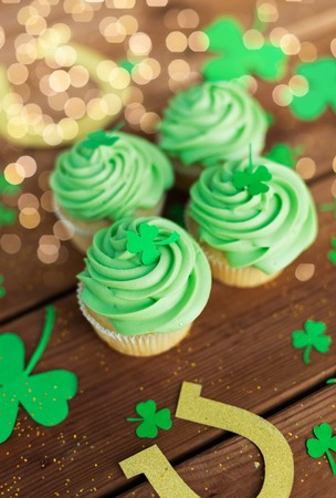 st patricks day, holidays and cooking concept - green cupcakes, horseshoes and shamrock on wooden table Stok Fotoğraf