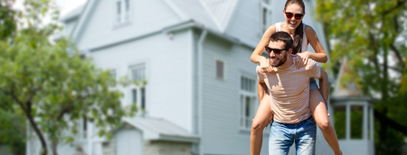 real estate and people concept - happy couple having fun in summer over house background Stok Fotoğraf - 116016329