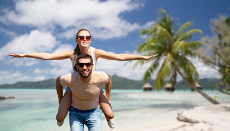 travel, tourism and people concept - happy couple having fun in summer over tropical beach background in french polynesia 免版税图像