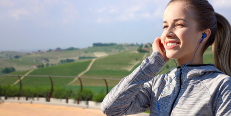 fitness, sport and people concept - happy woman listening to music in earphones over country landscape background Stock Photo