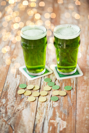 st patricks day, holidays and celebration concept - glasses of green beer and gold coins on wooden table Stok Fotoğraf