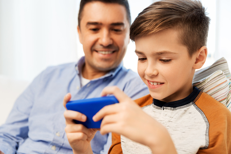 leisure, technology, family and people concept - happy father and son with smartphone playing game at home