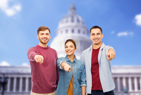 friendship and people concept - group of smiling friends pointing at you over capitol building background