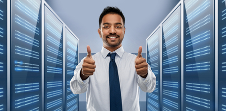 business, technology and data concept - smiling indian businessman in shirt with tie showing thumbs up over server room background Stock Photo
