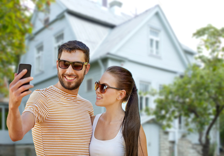 couple taking selfie by smartphone over house Stockfoto