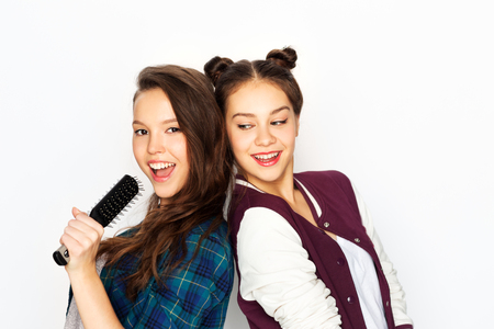 teenage girls singing to hairbrush and having fun