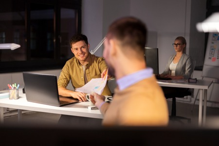 man giving papers to colleague at night office