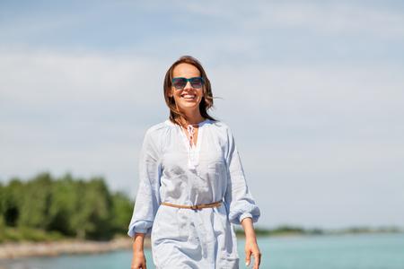 happy smiling woman walking along summer beach