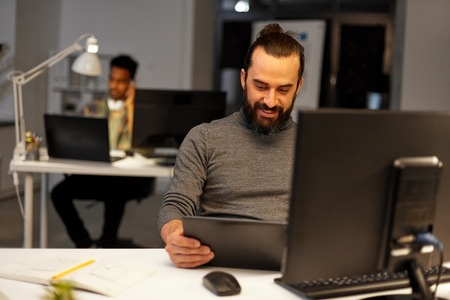 creative man with computer working late at office