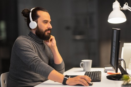 creative man in headphones working at night office Reklamní fotografie