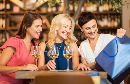 women with shopping bag at wine bar or restaurant Stock Photo