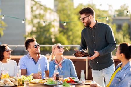 amici alla festa barbecue sul tetto in estate