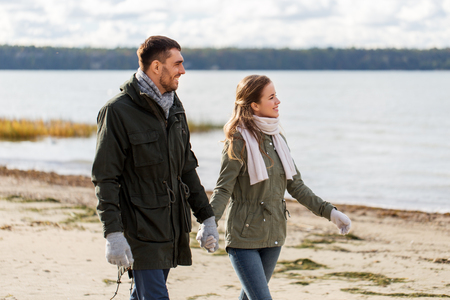 couple walking along autumn beach