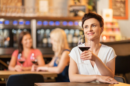 happy woman drinking red wine at bar or restaurant Stock Photo