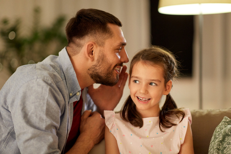 happy father whispering secret to daughter at home Standard-Bild