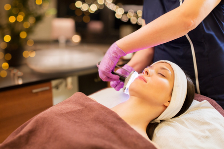 people, beauty, cosmetic treatment, cosmetology and technology concept - beautician with microdermabrasion device doing face exfoliation to young woman lying at spa parlor Imagens