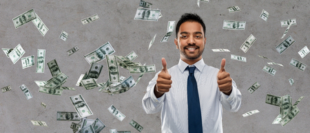 business, office worker and people concept - smiling indian businessman showing thumbs up over money rain on grey background
