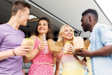 happy friends with drinks eating at food truck Stock Photo