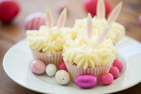 cupcakes with easter eggs and candies on plate