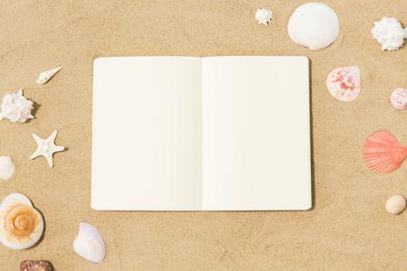 notebook with seashells on beach sand