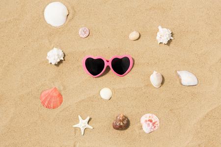 heart-shaped sunglasses and shells on beach sand