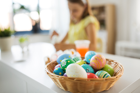 colored easter eggs and girl on background at home