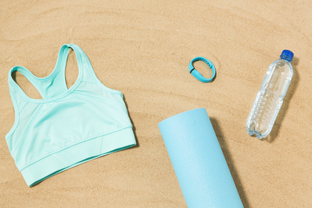 sports top, mat, fitness tracker and water bottle