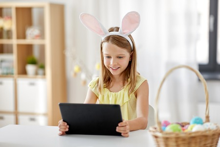 happy girl with tablet pc and easter eggs at home