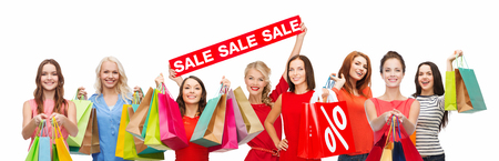 outlet and discount concept concept - happy women with shopping bags and sale sign over white background Reklamní fotografie
