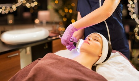 people, beauty, cosmetic treatment, cosmetology and technology concept - beautician with microdermabrasion device doing face exfoliation to young woman lying at spa parlor Zdjęcie Seryjne
