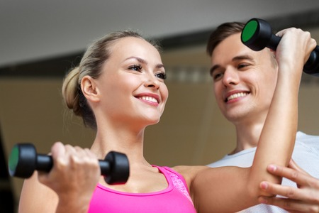 sport, fitness and people concept - smiling woman with personal trainer with dumbbells exercising in gym
