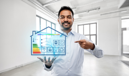 automation, internet of things and technology concept - smiling indian businessman or realtor with smart home virtual projection over empty office room background