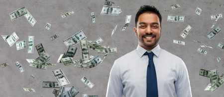 business, office worker and people concept - smiling indian businessman over money rain on grey background Stock Photo