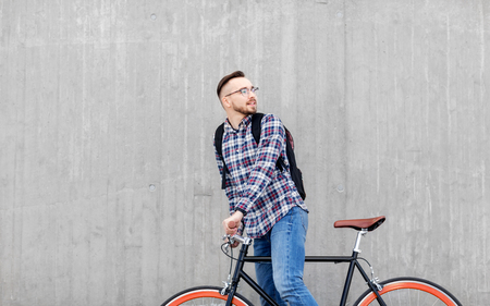 travel, tourism and lifestyle - happy young hipster man in earphones with fixed gear bike and backpack on city street Reklamní fotografie