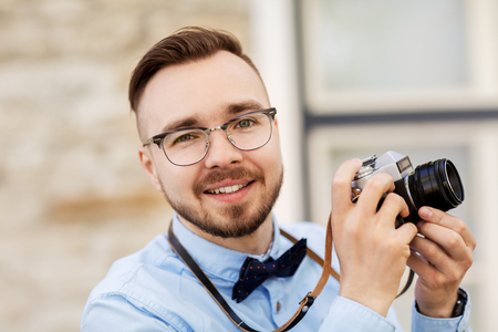photography, technology and lifestyle - young photographer or hipster man with vintage film camera outdoors Stock Photo